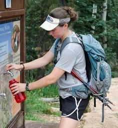 girl filling water bottle before hike