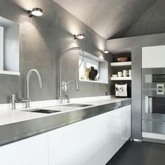 Bright Kitchen Design With Standing Stainles Steel Faucet And Sink On A Cabinet In White Color Also Wall Socncess On Gray Wall On The Side Of Shelves Also Modern Tools