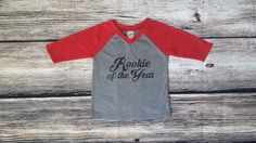 Celebrate your little guys first birthday with a special Rookie of the Year raglan t-shirt personalized with his name!  This baseball v neck tee is super soft and light weight made of 60% cotton and 40% polyester and features Rookie of the Year on the front side and age and name on the back!  Shirt color and vinyl can be personalized with the available color options. Picture shown is red/gray shirt with black vinyl.  Vinyl Color Options: black/red/blue/white  *Please inclu...