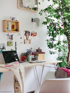 Home office com mesa de cavalete e tampo de madeira clara e muitas plantas.