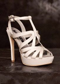 A wear-again staple, this White by Vera Wang strappy pump features a crystal baguette buckle.   Strappy satin caged platform sandal with crystal detail.  Heel height measures 4 3/4 inches.  Available in Ivory. Sizes 5-12.  Imported.