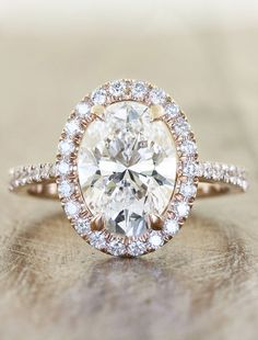 Exuding vintage charm, this alluring oval cut diamond halo ring has an old soul. The centerpiece is a 2.10ct oval cut diamond with the most enchanting cut and pleasing shape. The two carat stone is GIA graded at H-SI.