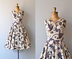 Vintage 1950s pale tan cotton dress with blue and brown batik-style floral print, high surplice bodice, fitted bodice, nipped waist, full skirt and