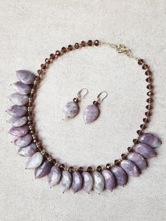 Natural Violet Drop Jade with Brown Crystal and Silver Round Spacer Necklace and Earrings   Length - 50cm (20inch)  Jade is a stone of the heart. As such it is related to the heart chakra and has a beneficial effect on all heart chakra related issues. So, of course, it can attract and enhance love of all kinds. It is also a stone of fidelity and generosity. It is also considered to be good for the physical heart and for emotional balance and stability. Jade is also very helpful as a stone of…