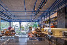 שבכה דומיננטית ממתכת נצבעה בכחול והיא מקשרת בין חלקי המסעדה: אלמנט תצוגה של מוצרי מזון וכלי הגשה, שצומח מהרצפה ומורכב על הקיר, מתפשט לכיוון התקרה ושם הוא משמש כמאחז לגופי תאורה, ואז ממשיך לעבר שביל הגישה, מקרה אותו ומוביל לגינה האחורית ( צילום: עמית גרון )