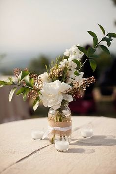 white tablecloths with natural burlap toppers.  pretty centerpieces from wyn & MM wedding.