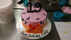 A nine inch cake with fondant numbers, bow, and minimalist music note decor.