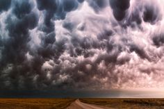 Mammatus clouds glow various colors over a dirt road in Friona, Texas during a severe thunderstorm in May, 2014. (Mike Mezeul II/Caters News)