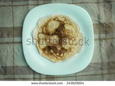 White plate with pancake on table - stock photo