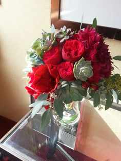 Hand-Tied bouquet featuring red amaryllis, red piano garden roses, red roses, red dinner plate dahlias, assorted succulents and seeded eucalyptus.