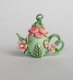 This miniature simply sweet fairy flower house teapot is a one of a kind original design and creation by artist C. Rohal. It is completely hand