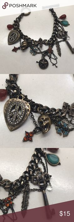 Lucky Brand rocker charm  bracelet There are so many moving parts to this bracelet- peace pick, skull, key, cross, charms and chains that hang- it has an antique look. Lucky Brand Jewelry Bracelets