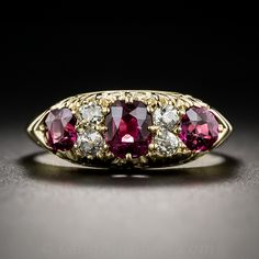 A glistening trio of deep, rich, wine red Siamese rubies (natural, no-heat), totaling 1.30 carats, are interspersed with pairs of old mine-cut diamonds in this very lovey late-Victorian ring, beautifully handcrafted in 18 karat yellow gold. The side gallery of this classic 'carved' ring is adorned with a graceful decorative open scroll design. A ravishing and romantic jewel, circa early twentieth century, from Great Britain. Accompanied with a gemological report from Stone Group Labs…