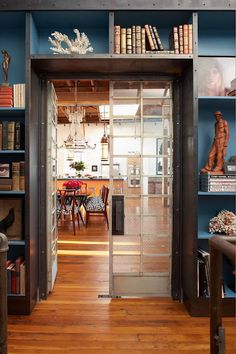 I LOVE the built in bookcases framing the passageway.  Also the most likely salvaged swinging glass doors are stunning and funky