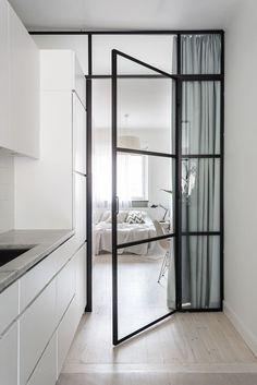 Glass door between kitchen bedroom, light hardwood floor.