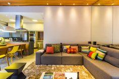 O sofá em L aproveita o layout da sala e proporciona um lugar aconchegante para assistir à TV. Na parede ao lado, um espelho dá sensação de amplitude.