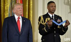 President Donald Trump (L) stands at attention during the reading of the citation prior to bestowing the Medal of Honor on retired US Army…