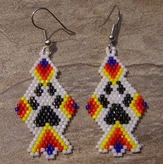 These wolf paw earrings are made in the brick stitch with size 11 delica seed beads. The colors that I have used are dark red, orange, yellow, dark blue, black, and white. The measure 1 3/4 long. The designer is Beadintrigue.