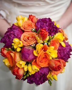 Mrs. Lox's wedding bouquet of bright pink peonies, yellow freesia, and orange tulips and roses.