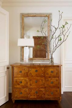 Chic foyer features a gray and gold mirror placed over a 9 drawer chest topped with a vase full of branches.