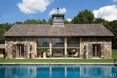 Designed by architect Gil Schafer, a Connecticut poolhouse takes the shape of a sophisticated barn with stone walls and weathered plank shutters; the custom-made windows are by Reilly Windows & Doors. The landscape design is by Deborah Nevins.