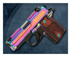 The Sig Sauer P238 pistol with a Rainbow Titanium finish.   Diminutive .380 ACP pistol comes in a variety of finishes, with the Rainbow Titanium Special Edition being the latest offering.  The grips are redwood. Just a fraction of the size of full-size. Small handgun built with the same accuracy and reliability as large frame SIG SAUER pistols. Overall length of 5.5 in, height of 3.96 in & weighing 15.2 ounces, SIG SAUER P238 is the ultimate firepower in an all metal frame concealed pistol.