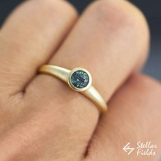 Round bezel ring in 14k yellow gold and a blue green natural Montana sapphire