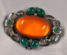 Sterling Silver, Amber, and Green Onyx Brooch, Georg Jensen, centering a large oval cabochon amber within floral and foliate frame, cabochon green onyx highlights, lg. 2 in., no. 78, signed Georg Jensen in circle of dots, Denmark