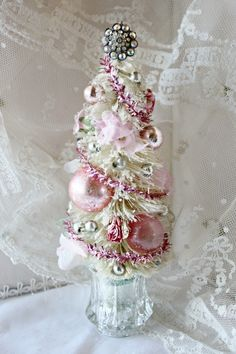 """about 11"""" tall    This white bottle brush tree has been glittered with mica flakes and decked out with sweet pink roses and vintage millinery petals. The pink foil garland is vintage, as are the silver mercury glass beads and shiny brite balls.    It is topped with a glittering aurora borealis rhinestone bit salvaged from old earrings and sits in an antique crystal toothpick holder."""