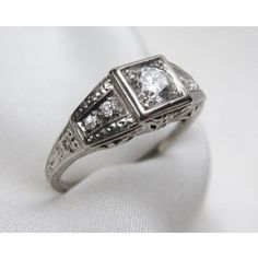 Circa 1930. This is a beautiful Art Deco diamond platinum engagement ring. The center stone is a .50 carat transitional cut diamond with an I1 clarity and J color. Accenting the center stone are (4) four Old European cut diamonds with a .06 carat total diamond weight, I1 clarity and K-J color. The ring is hand engraved. It weighs 3.68 grams.  Appraised Value: $4,200.