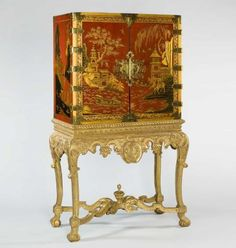 Early 18th century red japanned cabinet. Each panel is decorated with fantastical gilt landscapes of traditional types.