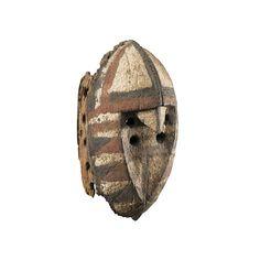 Masque, Mossi, Burkina Faso | lot | Sotheby's - Cet ancien masque wan-silga (ou « masque de l'épervier ») relève d'un style développé dans le sud-ouest du pays Mossi (ancien royaume de Ouagadougou), chez les Mossi Sukomsé. Dans une rigueur géométrique confinant à l'abstraction – accentuée par les motifs polychromes envahissant la surface -, l'oiseau n'est identifié que par les lignes cinglantes du bec sculpté à l'aplomb de la face épannelée et de l'étroite crête sagittale.
