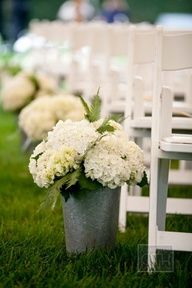 Path lined with plain galvanized buckets of white hydrangea and lush green ferns. These bunches could be used again during reception as rustic centerpieces or as embellishments on bar or dessert table.    Having an indoor affair? Switch out the metal bucket for a sleek white enamel or silver vessel.
