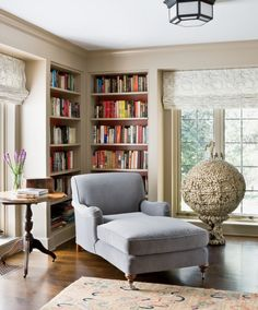 In the library, a cozy corner with built-in bookcases, a comfortable chaise lounge, round side table, and large art piece by Chinese artist Tao Xue; photography: Angie Seckinger