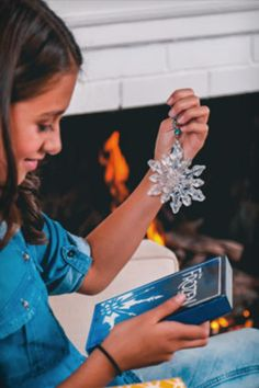 Snowflake Ornament: This glass ornament has an iridescent finish and wire hanger, featuring a metal snowflake and blue translucent gems. Includes closed box with magnetic opening. Snowflake Ornaments, Glass Ornaments, Snowflakes, Wire Hangers, Iridescent, Theatre, Frozen, Gems, Metal