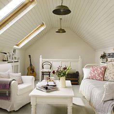 neat attic living room: love the white wooden ceiling and the windows. via House to home