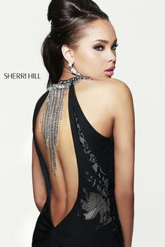 Get rock and roll chic in this daring gothic inspired Sherri Hill 21363 . Triangular lace panels create a chic cut out design over the bodice while the neckline loops to a keyhole opening that shows a little cleavage.