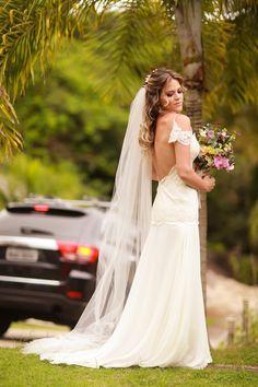 Noiva em vestido fluido Trinitá para casamento na praia com leve manga de renda e véu. Cabelo solto e Buque em tons de rosa.
