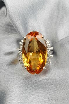 18kt White Gold and Imperial Topaz Ring, prong-set with an oval-cut Imperial topaz measuring approx. 26.00 x 14.20 x 9.50 mm, flanked by full- and tapered baguette-cut diamonds, size 7.
