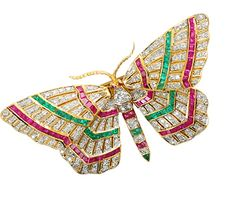 This 20th century stylized butterfly brooch of 18k yellow gold is encrusted from head to tip of its abdomen with precious jewels. Patterned with colorful bands, one hundred sixty-three (163) brilliant cut diamonds with a total estimated weight of 1.7 carats, sixty-six (66) rubies plus two (2) cabochon ruby eyes of an estimated total of .50 carats and forty (40) natural emeralds of about .35 carats flaunt their intense colors in an animated play of the forewings.