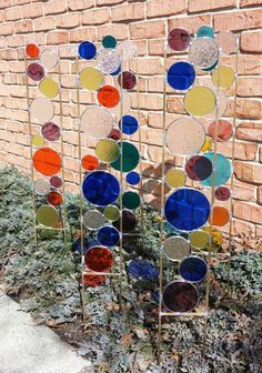 """Stained glass garden art stake in blue, chartreuse green and grape. Made from transparent and clear textured glass with a solid brass frame. Texture of the colored glass may vary, but the colors and placement will be the same. The glass section is 24"""" and the legs are 10"""" long, giving you lots of length to stick in the ground. Overall dimensions are 4"""" wide and 34"""" tall. The last couple of photos are other stakes I have created nestled in a garden setting. The garden art stakes begin by me…"""