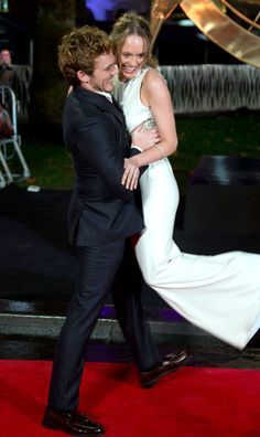 British actor Sam Claflin picks up wife and actress Laura Haddock as they arrive on the red carpet.