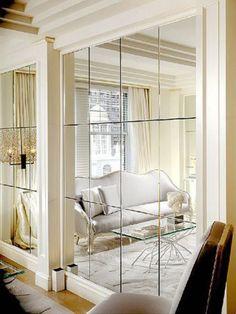 Parede de espelhos na decoração, nesse ambiente a paginação dos espelhos em quadrados refletindo o outro ambiente .