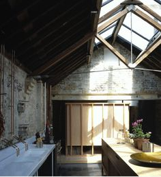 Exposed truss, skylights, raw bricks. And love the exposed pipe taps!