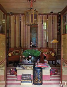Cole Park, the manor that designer Anouska Hempel shares with her husband, Sir Mark Weinberg, in the countryside of Wiltshire, England, dates from the mid-16th century. A profusion of books and decorative objects top an ottoman in the reception room.  For details see Sources.
