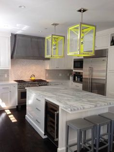 Grey and white with a pop of bright yellow.  Classic touches such as the subway tile backsplash and marble herringbone accent keep this kitchen grounded.