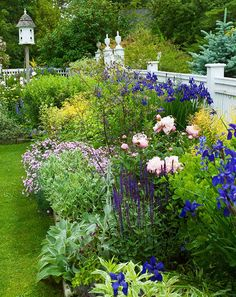 Beautiful backyard border created with flowering shrubs and perennials.  A wonderful bird house focal point. www.BlueSkyRain.com #irrigation #sprinklers #landscape #lighting #flowers #garden