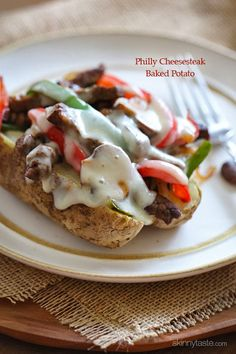 Quick skillet steak with onions, peppers and mushrooms are loaded on top of a baked potato and topped with melted cheese – this is awesome a...