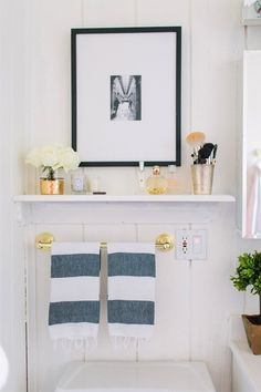 source: The Every Girl      Alaina Veronica Kaczmarski Home - Gorgeous bathroom features over the toilet shelf filled with fragrances paired with black and white photo framed in black gallery frame. Below bathroom shelf is polished brass towel bar and West Elm Hammam Stripe Hand Towels.