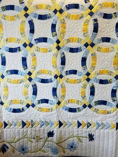 This stunning queen Wedding Ring quilt features a border of blue and yellow appliqued flowers around the wedding rings. It is hand quilted by a local Mennonite woman.